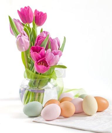 Foto de Florero de vidrio con coloridos tulipanes y huevos de pintura de Pascua con espacio de copia - Imagen libre de derechos