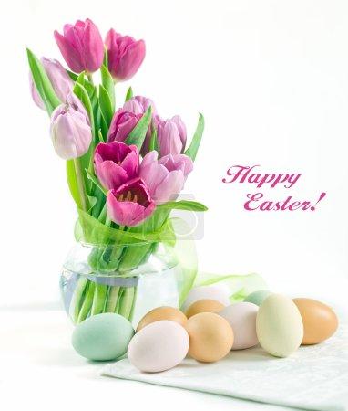 Foto de Florero de vidrio con coloridos tulipanes y huevos de pintura de Pascua con filtro verde - Imagen libre de derechos