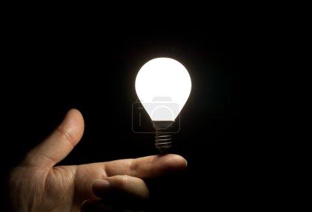 Lit light bulb balancing on finger