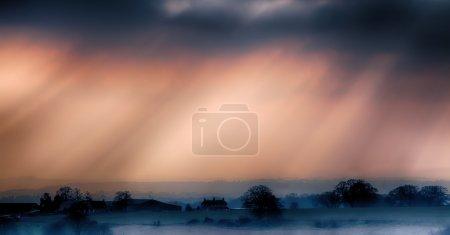 Photo pour Coucher du jour sur un paysage agricole brumeux - image libre de droit