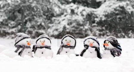 Photo for Little snowmen in a group carol singing in the snow - Royalty Free Image