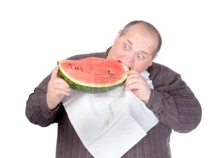 Fat man tucking into watermelon