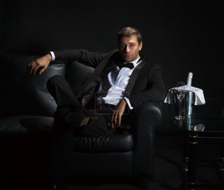 Photo for Sexy handsome man in tuxedo sitting in the darkness of a nightclub with an unopened bottle of champagne on ice waiting for his date - Royalty Free Image