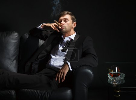 Photo for Macho man in a stylish tuxedo sitting in the darkness at a nightclub puffing on a cigar and drinking brandy or cognac - Royalty Free Image