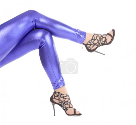 Photo for Cropped view image of a woman's sexy legs clad in shimmering blue leggins and stilettos - Royalty Free Image