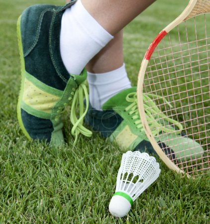 Photo for Foot of sportswoman who plays badminton on grass - Royalty Free Image