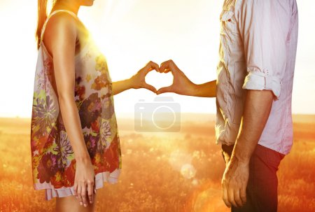 Photo for Silhouette of hands in form of heart when sweethearts have touched - Royalty Free Image