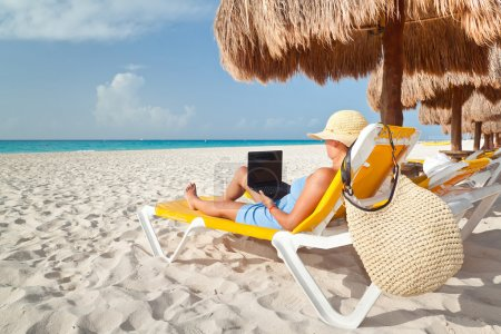 Photo for Woman with laptop relaxing on the deck chair at the Caribbean sea - Royalty Free Image