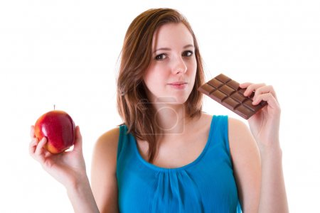 Photo for An apple and chocolate bar choice of young beautiful brunette - Royalty Free Image