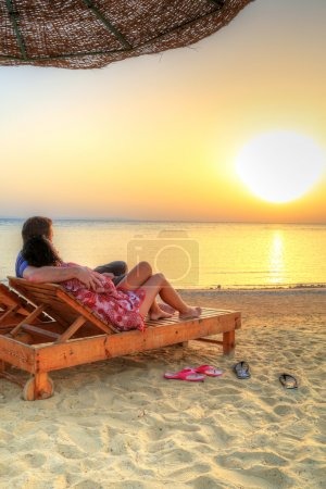 Couple in hug watching together sunrise on the beach