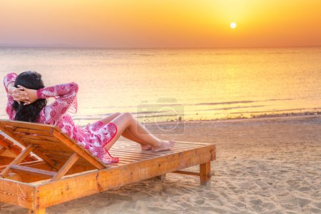 Beautiful woman relaxing at sunrise over Red Sea