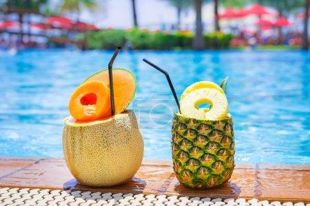 Photo pour Ananas et melon des cocktails au bord de la piscine - image libre de droit