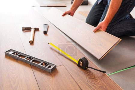 Photo for Man installing new laminated wooden floor - Royalty Free Image