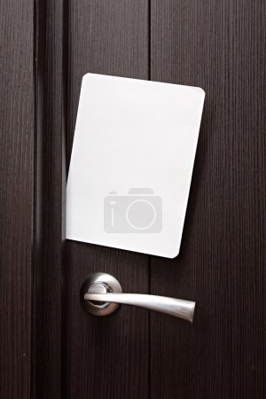 White envelope with message slipped under wooden door. Blank paper to write a nested in the gap under the wooden door.