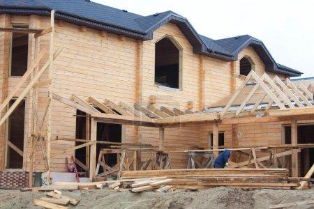 Photo pour Les travailleurs tailler le toit de la maison en bois - image libre de droit