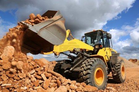 Photo pour Chargeur frontal dumping de Pierre et sable dans les carrières minières - image libre de droit