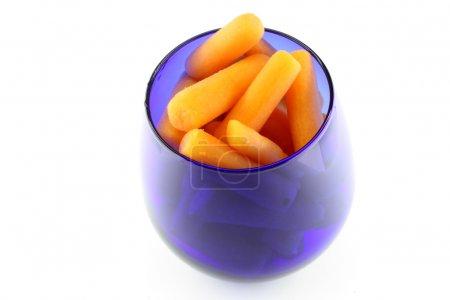 Photo pour Verre bleu avec carottes sur le fond blanc - image libre de droit
