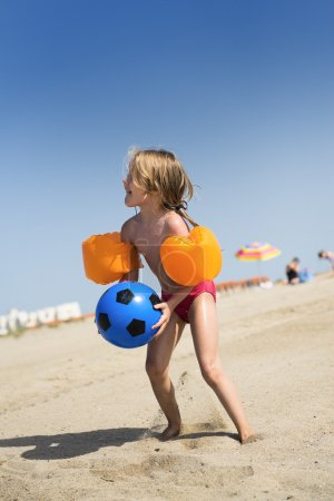 Photo for Young little girl is having fun with a baloon on the beach in summer - Royalty Free Image