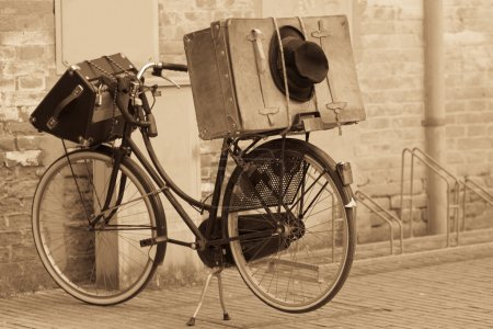 Shabby black hat and suitcases on the bike