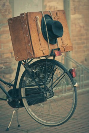 Black hat and brown suitcase on old bike