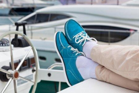 Beine in Hosen und hellblaue Topsider auf Jacht