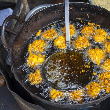 Photo for Indian vada (cake), fried in the oil, street food - Royalty Free Image