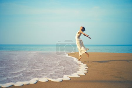 Photo for Young lady in white dress jumping on the beach - Royalty Free Image