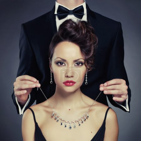 Photo for Elegant man on a beautiful woman wears a necklace - Royalty Free Image