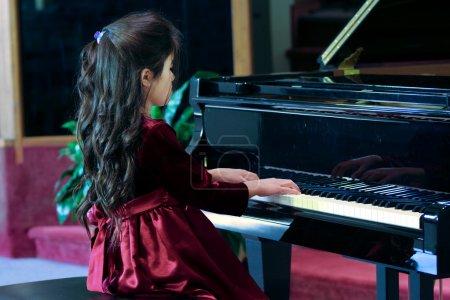 Photo pour Enfant jouant piano à queue - image libre de droit