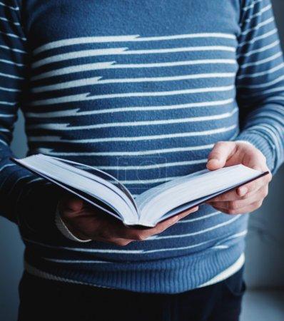 Photo pour Un homme qui lit. Livre dans ses mains . - image libre de droit