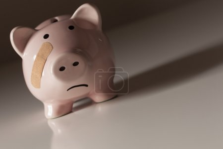 Photo for Piggy Bank with Bandage on Face on Dramatic Gradated Background. - Royalty Free Image