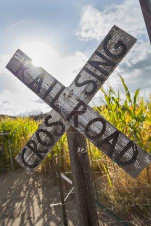 Photo pour Ancien panneau de passage à niveau de chemin de fer de campagne près d'un champ de maïs dans un cadre rustique extérieur - image libre de droit