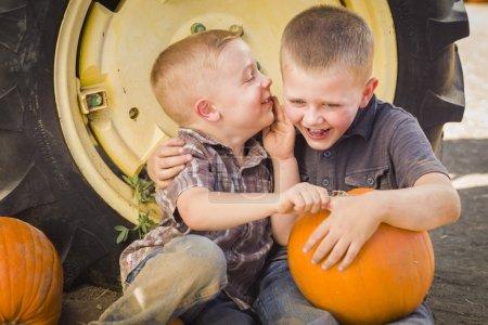 Foto de Dos chicos sentado contra un tractor de llantas con calabazas y susurrando secretos en rústico. - Imagen libre de derechos