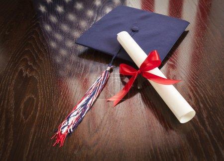 Graduiertenmütze und Dipoma auf dem Tisch mit Reflexion der amerikanischen Flagge
