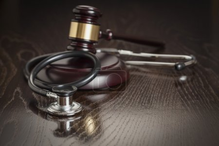 Gavel and Stethoscope on Reflective Wooden Table....