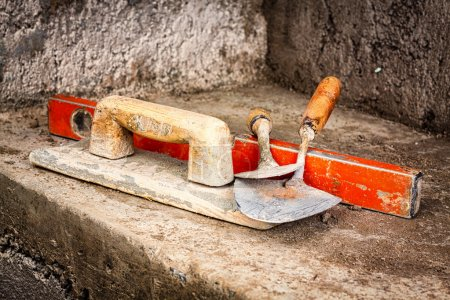 Photo for Trowels and other masonry tools on an unfinished concrete wall background - Royalty Free Image