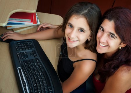 Hispanic mother and her daughter working on a computer
