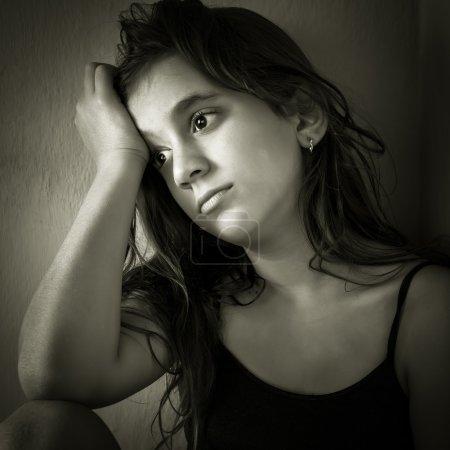 Sad hispanic girl sitting in a corner