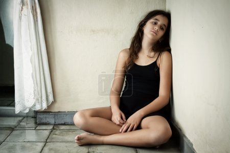 Photo for Grunge image of a sad and lonely latin girl sitting in the corner of a dirty house - Royalty Free Image