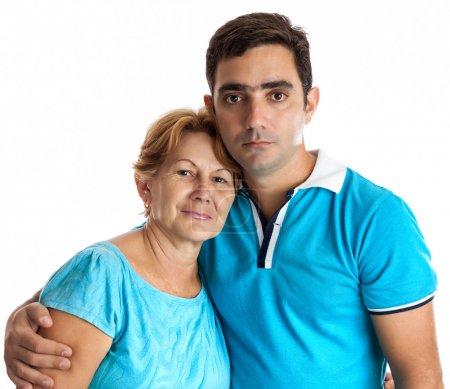 Photo pour Jeune homme hispanique étreignant sa mère isolée sur blanc - image libre de droit