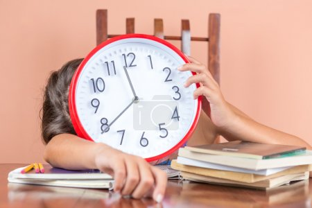 Tired child sleeping and holding a clock