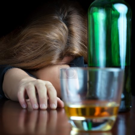 Photo for Drunk alcoholic woman sleeping on a table with a glass and a bottle of scotch - Royalty Free Image