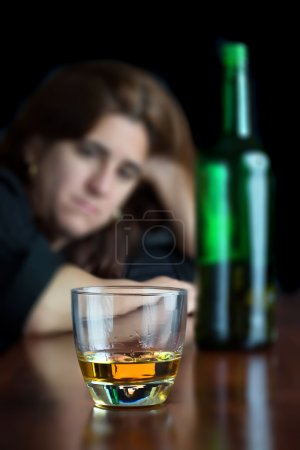 Photo for Portrait of a drunk hispanic woman drining alone (on a dark background) - Royalty Free Image