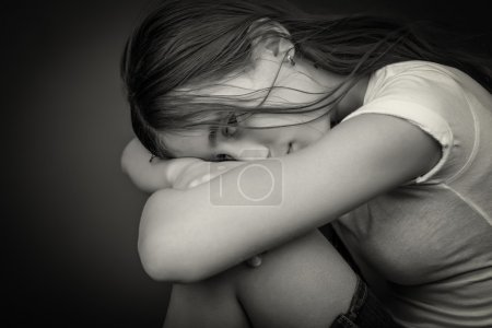 Photo for Black and white image of a sad and lonely girl with her head resting on her legs and looking at the camera - Royalty Free Image