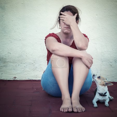 Photo for Sad adult woman crying with a small dog besides her - Royalty Free Image