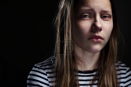 Photo for Dark portrait of a crying teen girl, studio shot - Royalty Free Image