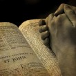 Hands of a person raised together in prayer with b...