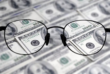 Photo for Closeup of several hundred dollar bills isolated on white background with glasses to bring money into focus - Royalty Free Image