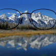 Glasses with clear vision of Teton Mountains in ba...