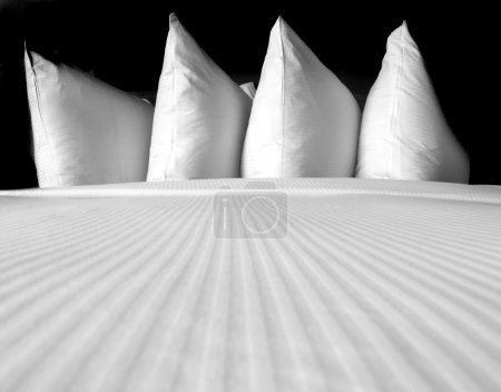 Group of several white pillows on a comfortable be...